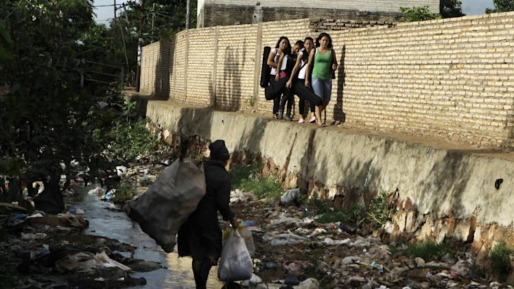 "In this Dec. 11, 2012 photo, young women carry their instruments along the edge of a polluted stream where a woman scavenges for recyclable goods in the garbage, as they head to their practice session with ""The Orchestra of Instruments Recycled From Cateura,"" in Cateura, a vast landfill outside Paraguay's capital of Asuncion, Paraguay.  The community of Cateura could not be more marginalized. But the music coming from garbage has some families believing in a different future for their children. (AP Photo Jorge Saenz)"