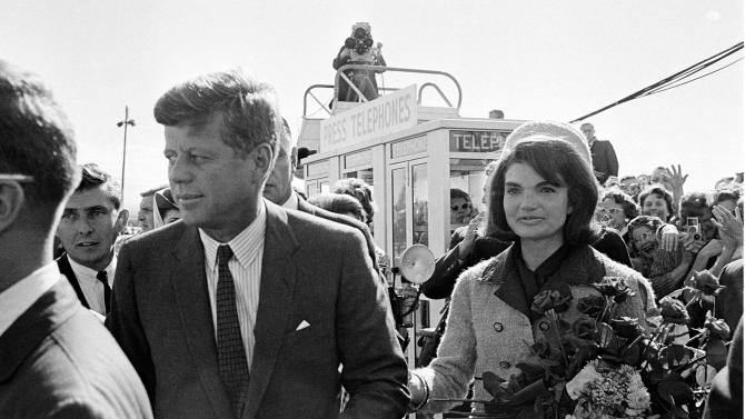 FILE - In this Nov. 22, 1963 file photo, President John F. Kennedy and his wife, Jacqueline Kennedy, arrive at Love Field airport in Dallas, as a television camera, above, follows them. More than a dozen new documentary and information specials are among the crop of TV commemorations pegged to this half-century mark of a weekend when, as viewers will be reminded again and again, everything changed. (AP Photo/File)