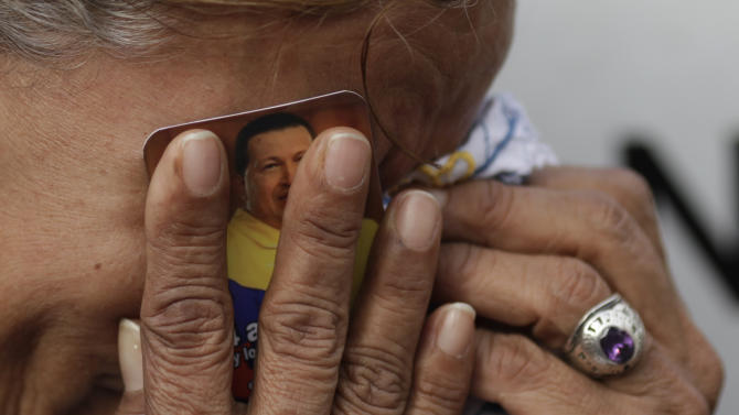 A woman holds a picture of President Hugo Chavez against her face as she cries outside the military hospital where he died Tuesday in Caracas, Venezuela, Wednesday, March 6, 2013.  Seven days of mourning were declared, all school was suspended for the week and friendly heads of state were expected  for an elaborate funeral Friday..(AP Photo/Ariana Cubillos)