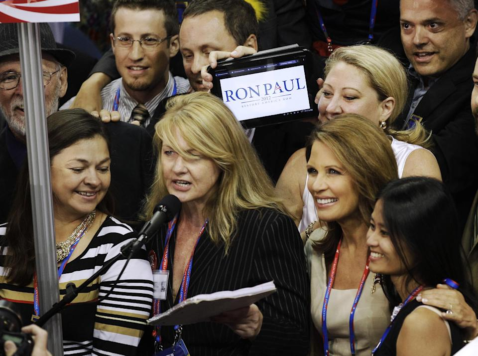 Minnesota Representative Michele Bachmann, second right, listens as Minnesota delegates casts their vote during the Republican National Convention in Tampa, Fla., on Tuesday, Aug. 28, 2012. (AP Photo/Charlie Neibergall)