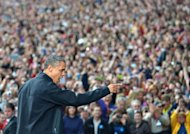 US President Barack Obama gestures to supporters as he arrives at a campaign rally October 4, 2012 at the University of Wisconsin- Madison in Madison, Wisconsin