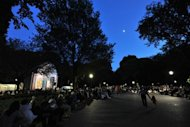 "People attend a free performance of Giacomo Puccini's ""Tosca"" by the New York Grand Opera at Central Park's Naumburg Bandshell (L) on June 27 in New York. Conductor Vincent La Selva and his company have been presenting free opera in Central Park since 1974"