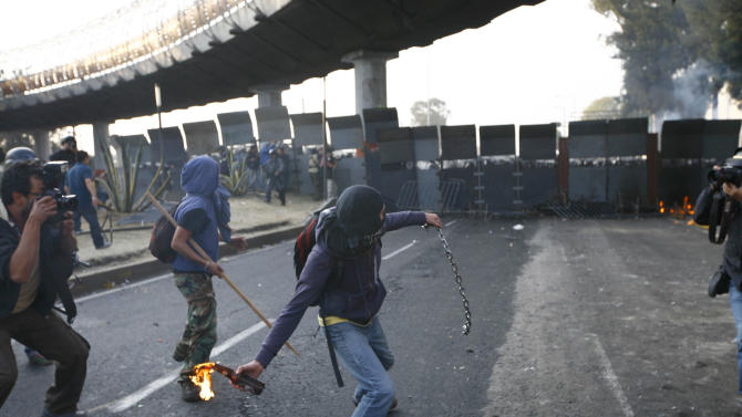 A protestor throws a fire bottle over steel security barriers around the National Congress, where the swearing in of new Mexican President Enrique Pena Nieto will take place in Mexico City, Sunday, Dec. 1, 2012.  Pena Nieto took power at midnight in a symbolic ceremony and will formally take the oath of office Saturday morning after campaigning as the face of a new PRI _ a party that claims to be repentant and reconstructed after voted out of the presidency in 2000.(AP Photo / Marco Ugarte)