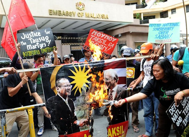 AFP photo: Protesters burn a portrait of Philippine President Benigno Aquino (L) and Malaysian Prime Minister Najib Razak (R) in front of the Malaysian embassy in Manila on March 5, 2013.