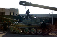 In this Monday, Nov. 19, 2012 file photo, Syrian fighters stand on a tank they took after storming a military base in Aleppo. Through mid-2012, rebel power grew and Assad&#39;s army ramped up its response. Relentless government shelling leveled neighborhoods and killed hundreds. Regular reports emerged of mass killings by the regime or thugs loyal to it, pushing more Syrians toward armed struggle. The government, which considers the opposition terrorist gangs backed by foreign powers, denied any role, and does not respond to requests for comment on its military. The rebels, too, were accused of atrocities. (AP Photo/ Khalil Hamra)