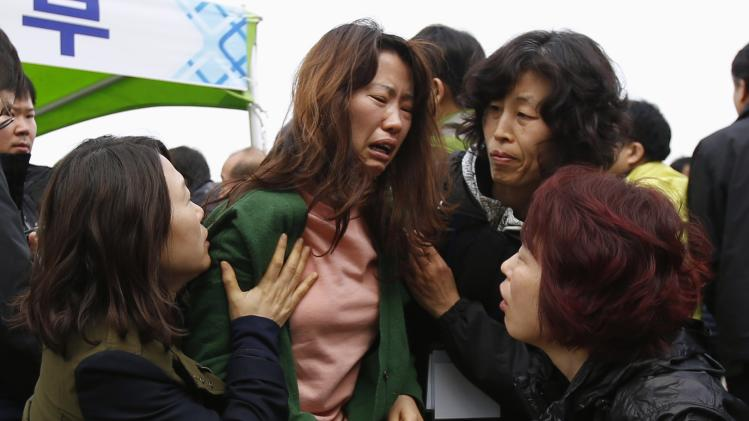 A family member of missing passengers who were on the South Korean ferry Sewol which sank in the sea off Jindo, cries as she found the name of her family in the list of fatalities, at a port in Jindo
