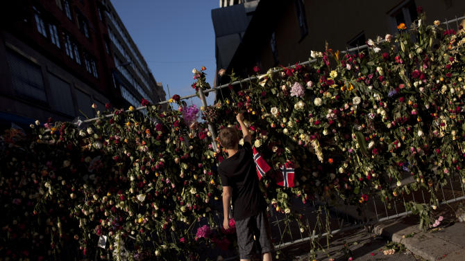 A boy places a rose on a fence surrounding the area where eight people were killed in Friday's blast in Oslo Wednesday, July 27, 2011.  (AP Photo/Emilio Morenatti)