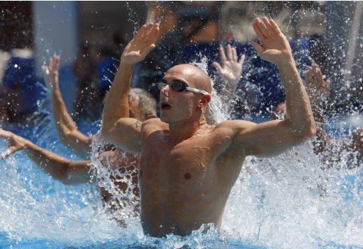 Competitors practice during a men's synchronized swimming competition at the EuroGames 2012 in Budapest