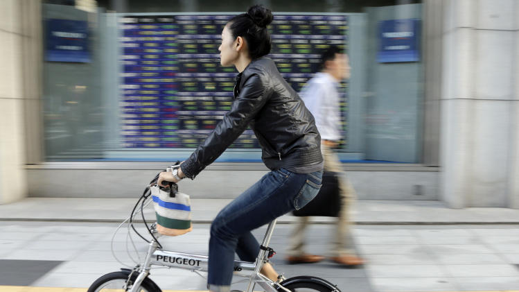 A woman pedals pasts an electronic stock board outside a securities firm in Tokyo, Friday, Oct. 26, 2012. Asian stock markets fell Friday after the latest data on U.S. housing dimmed hopes of improvement in an industry that is crucial to recovery in the world's No. 1 economy. Japan's Nikkei 225 index fell 0.9 percent to 8,973.97. (AP Photo/Koji Sasahara)