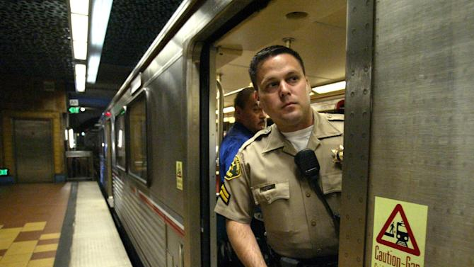 FILE - This July 7, 2005 file photo shows Los Angeles County sheriff's deputy Shawn Moreno patroling a Los Angeles subway. With 85 miles of track and 170,000 riders, the board of the county's Metropolitan Transportation Authority voted Thursday May 24, 2012, to make the system work like it does in every other big city by approving locking gates. (AP Photo/Jae C. Hong, File)