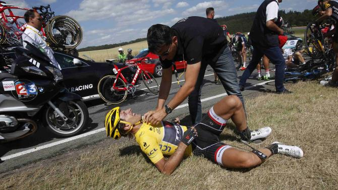 Race leader and yellow jersey holder Trek Factory rider Fabian Cancellara of Switzerland receives assistance as he lies on the ground after a fall during the third stage of the 102nd Tour de France cycling race from Anvers to Huy