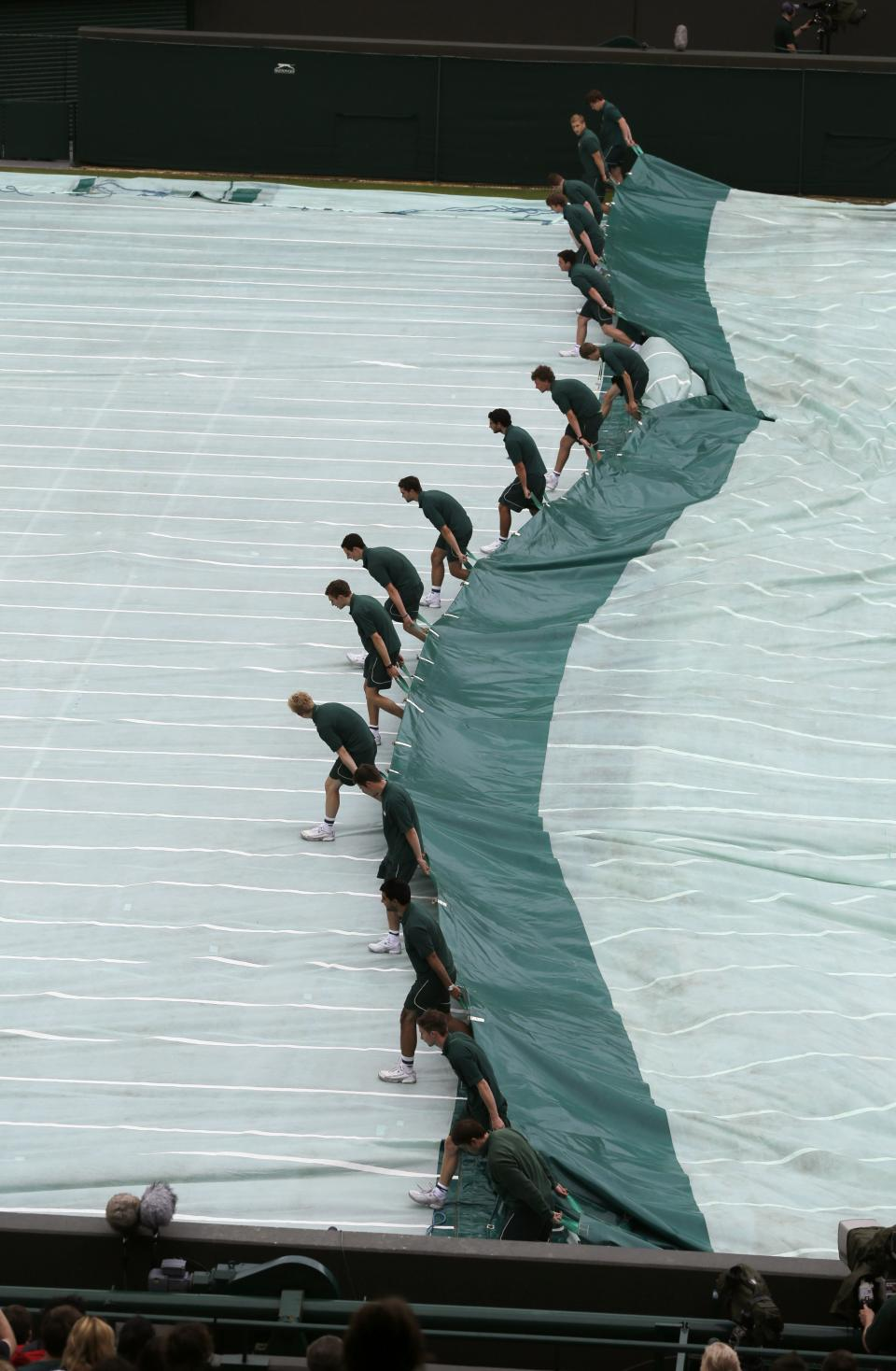 Ground staff pull the covers off following a rain delay to a first round men's singles match between Jo-Wilfried Tsonga of France and Lleyton Hewitt of Australia during a match at the All England Lawn Tennis Championships at Wimbledon, England, Tuesday, June 26, 2012. (AP Photo/Tim Hales)