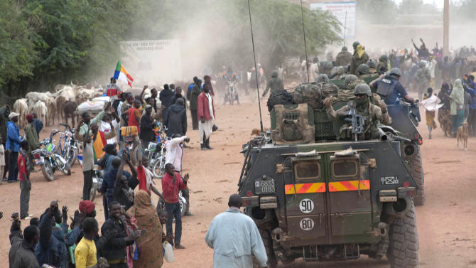 In this Monday, Jan. 28, 2013, photo provided by the French Army Communications Audiovisual office (ECPAD) and released Tuesday, Jan. 29, 2013, a crowd cheers the arrival of French soldiers in Timbuktu, in northern Mali. Backed by French helicopters and paratroopers, Malian soldiers entered the fabled city of Timbuktu on Monday after al-Qaida-linked militants who ruled the outpost by fear for nearly 10 months fled into the desert, setting fire to a library that held thousands of manuscripts dating to the Middle Ages. (AP Photo/French Army Communications Audiovisual office (ECPAD), Arnaud Roine)