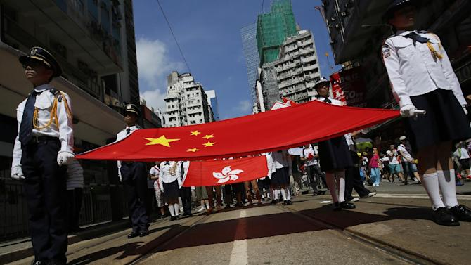 Participants hold a Chinese national flag and a Hong Kong flag as tens of thousands of people march on a down town street to oppose a planned civil disobedience campaign by pro-democracy activists in Hong Kong, Sunday, Aug. 17, 2014. The rally was organized by a pro-Beijing group. Many carried banners or shouted slogans saying they were opposed to the Occupy Central pro-democracy movement. (AP Photo/Vincent Yu)