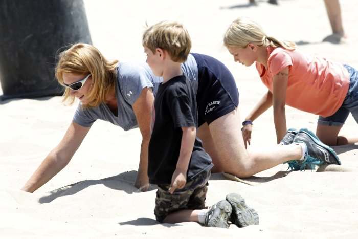 Chris Vernetti and her children search for one of 36 buried plastic Angry Bird orbs filled with hidden cash in Hermosa Beach, California May 31, 2014. (REUTERS/Jonathan Alcorn)