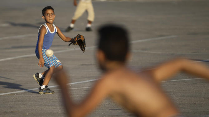 In this July 8, 2013 photo, children play baseball near the Latinoamericano Stadium in Havana, Cuba. For a place where most people earn just $20 a month at their government jobs, Havana can be a surprisingly expensive place to be a traveler. But there are plenty of free ways to have fun in this city known for sea, sun and salsa. (AP Photo/Franklin Reyes)