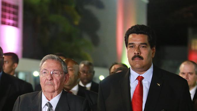 In this photo released by Miraflores Press Office, Cuba's President Raul Castro, left,  and Venezuela's Vice President Nicolas Maduro stand upon their arrival to the Fort Tiuna military academy to visit the coffin containing the body of Venezuela's late President Hugo Chavez during his wake in Caracas, Venezuela, Thursday, March 7, 2013. Maduro, Venezuela's acting president, said Chavez's  remains will be put on permanent display at the Museum of the Revolution, close to the presidential palace where Chavez ruled for 14 years. A state funeral for Chavez attended by some 33 heads of government is scheduled to begin Friday morning. (AP Photo/Miraflores Press Office)