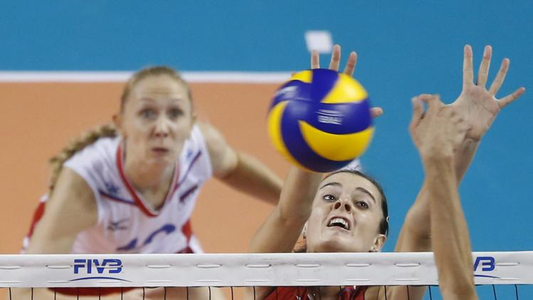 Yana Shcherban of Russia jumps to block the ball spiked by Gozde Sonsirma of Turkey during their FIVB Women's Volleyball World Grand Prix 2014 final round match in Tokyo