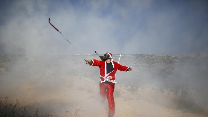 Palestinian protester uses a slingshot to return a tear gas canister fired by Israeli troops during clashes in the West Bank village of Bilin
