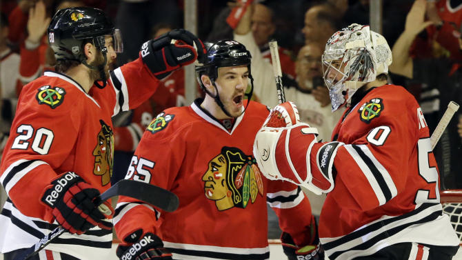 Chicago Blackhawks goalie Corey Crawford, right, celebrates with teammates Andrew Shaw, center, and Brandon Saad after they defeated the Detroit Red Wings 4-1 in Game 5 of the NHL hockey Stanley Cup playoffs Western Conference semifinals in Chicago, Saturday, May 25, 2013. (AP Photo/Nam Y. Huh)