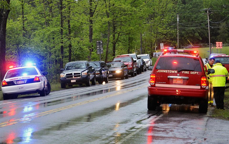 In this Friday, May 24, 2013 photo, rescue workers congregate across from the site of a plane crash in a wooded area off Route 10 in the town of Fulton in Ephratah, N.Y., after a small plane crashed killing two people. (AP Photo/The Daily Gazette, Peter R. Barber)