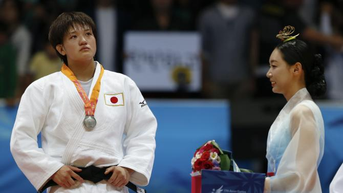 Arai reacts during the medal ceremony for the women's -70kg judo event at Dowon Gymnasium during the 17th Asian Games in Incheon
