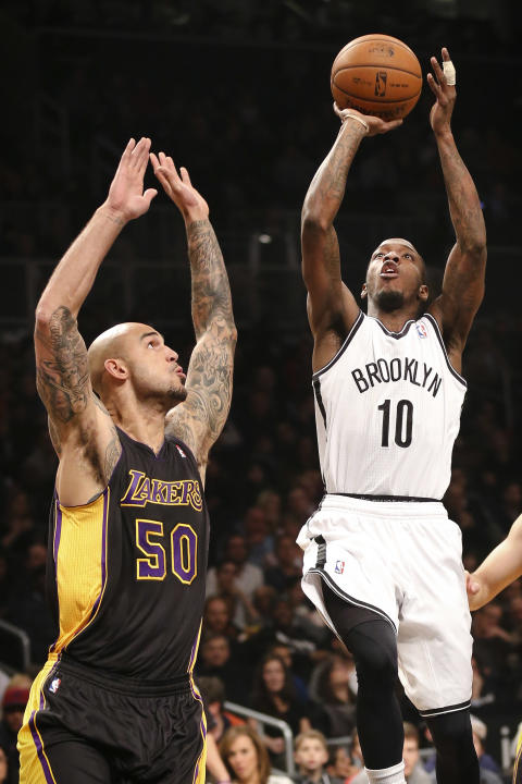 Brooklyn Nets point guard Tyshawn Taylor (10) shoots against Los Angeles Lakers center Robert Sacre (50) in the first half of an NBA basketball game at the Barclays Center, Wednesday, Nov. 27, 2013, i