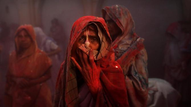 An Indian Hindu widows covers her face as colored powder is thrown in the air during Holi celebrations organized by the NGO Sulabh at the Meera Sahbhagini Ashram in Vrindavan, India, Wednesday, March 27, 2013. The widows, many of whom at times have lived desperate lives in the streets of the temple town, celebrated the festival for the first time at the century old ashram. After their husband's deaths the women have been banished by their families to the town where devotees believe Lord Krishna was born, for supposedly bringing bad luck. (AP Photo/Kevin Frayer)