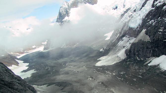 In this image provided by Drake Olson at flydrake.com, a landslide is seen at Glacier Bay National Park in Alaska on July 8, 2012.  When a cliff collapsed in Glacier Bay National Park, it sent rock and ice coursing down a valley and over a lovely white glacier in what could be one of the largest landslide recorded in North America.  The rumbling was enough so that it showed up as an earthquake in Alaska and Canada. (AP Photo/flydrake.com, Drake Olson)