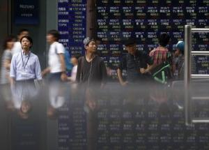Pedestrians standing in front of an electronic board showing the various stock prices outside a brokerage are reflected in a polished stone surface, in Tokyo