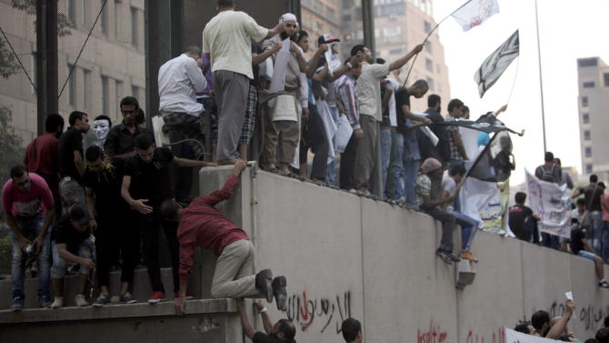 """Egyptian protesters climb the walls of the U.S. embassy with Arabic graffiti that reads """"any one but you God's prophet"""" during protests in Cairo, Egypt, Tuesday, Sept. 11, 2012. Egyptian protesters, largely ultra conservative Islamists, have climbed the walls of the U.S. embassy in Cairo, went into the courtyard and brought down the flag, replacing it with a black flag with Islamic inscription, in protest of a film deemed offensive of Islam. (AP Photo/Nasser Nasser)"""