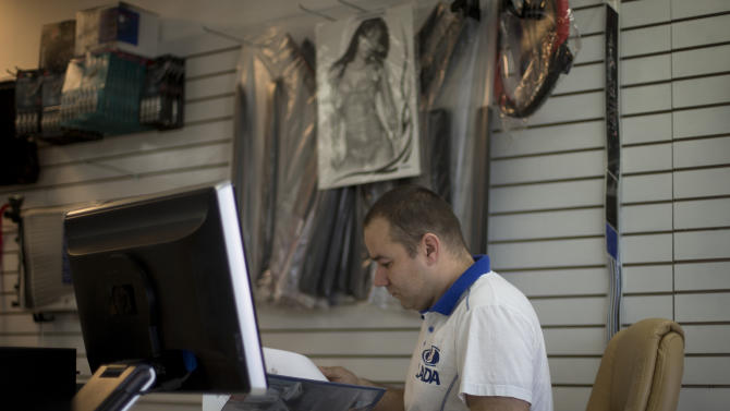 In this Feb. 12, 2013 photo, Fabian Zakharov sit at his computer ordering parts for a customer's Russian made car in his Hialeah, Fla. auto parts store. Zakharov, who was born in Russia but grew up in Cuba, learned how to drive in one of the two Ladas his parents own. He recalls driving throughout Cuba on family trips, rarely experiencing any problems or having it breaking down. The only trouble was affording gas. (AP Photo/J Pat Carter)