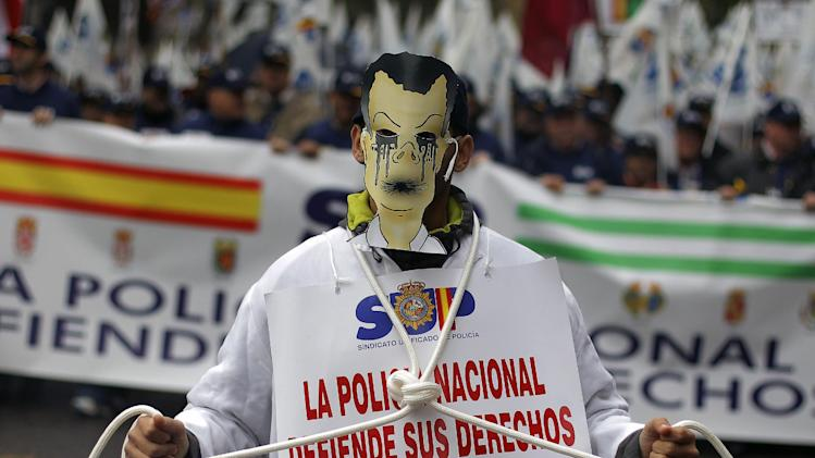 "A police officer marches carrying a banner reading, ""National police fights for its rights"" during a protest  against the government's austerity measures and the elimination of their Christmas bonus pay, one of 14 paychecks that most Spanish civil servants get each year, in Madrid, Spain, Saturday, Nov. 17, 2012. (AP Photo/Andres Kudacki)"