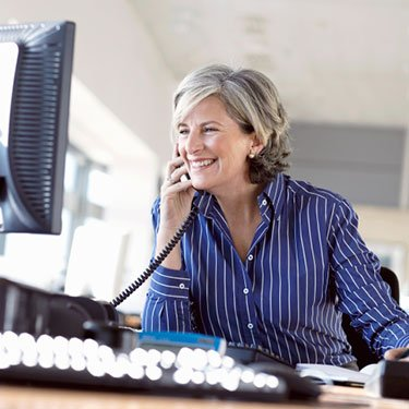 Mature-woman-using-telephone-at-desk-in-office_web
