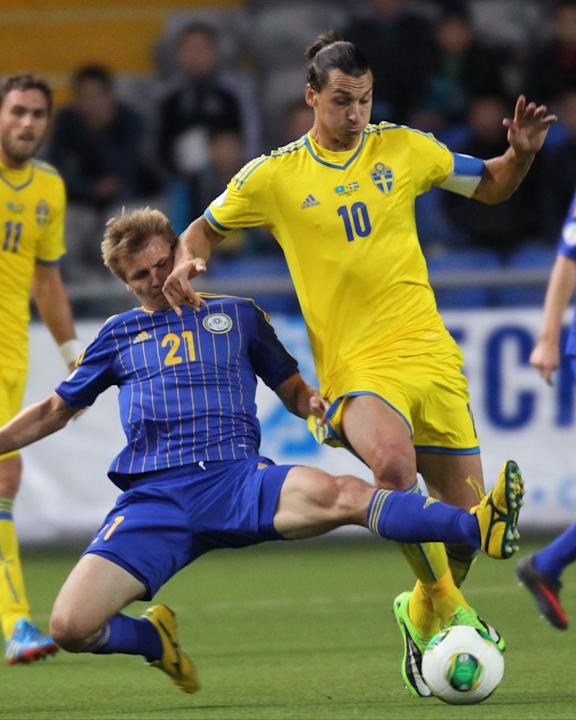 Kazakhstan's Valerij Korobkin, left, and Sweden's Zlatan Ibrahimovic fight for the ball during their World Cup group C qualifying soccer match in Astana, Kazakhstan, Tuesday, Sept. 10, 2013. (AP Photo