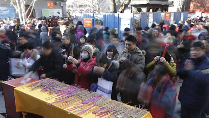 People holding incense pray for good fortune on the first day of the Chinese Lunar New Year of the Monkey in Beijing