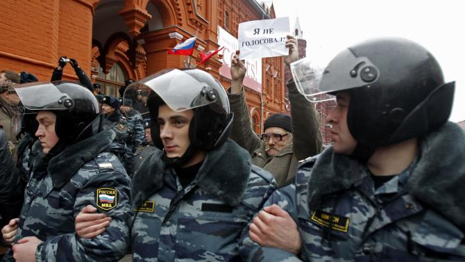 "A man holds up a banner reading ""I didn't vote,"" as Russian police officers detain opposition demonstrators during an unsanctioned pro-democracy rally in downtown Moscow, Sunday, Dec. 4, 2011. The rally was staged by a few dozen activists of the Left Front opposition group to protest against Sunday's elections. (AP Photo/Misha Japaridze)"