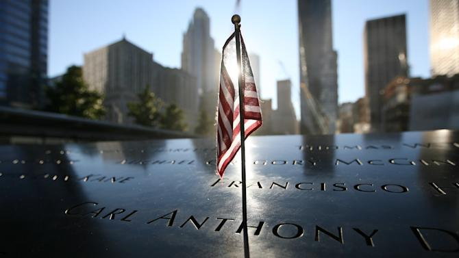 A small American flag is inserted in a name engraved at the north reflecting pool of World Trade Center Memorial, during observances on the 11th anniversary of the attacks on the World Trade Center, in New York, Tuesday Sept. 11, 2012. (AP Photo/Chris Pedota, Pool, The Record)