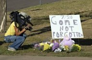 &lt;p&gt;A cameraman takes video of a memorial for victims near the theater where 12 people were killed July 20, in Aurora, Colorado. The masked, black-clad shooter, named as James Holmes, 24, burst into the movie theater barely 20 minutes into the midnight screening of &quot;The Dark Knight Rises&quot;, throwing two tear-gas type devices before opening fire.&lt;/p&gt;