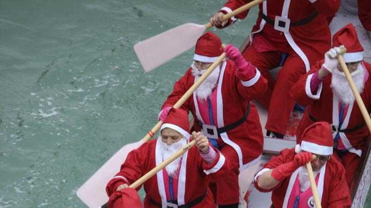 People dressed in Santa Claus costumes row a boat on the Venice canal