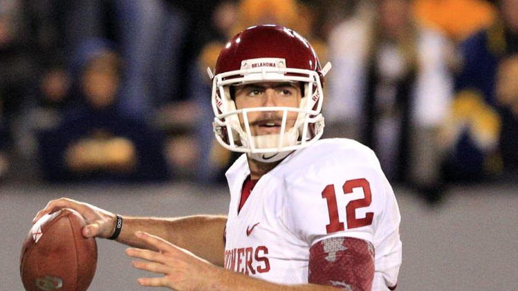 Oklahoma quarterback Landry Jones (12) attempts a pass during the third quarter of their NCAA college football game against West Virginia in Morgantown, W.Va., on Saturday, Nov. 17, 2012. Oklahoma won 50-49. (AP Photo/Christopher Jackson)