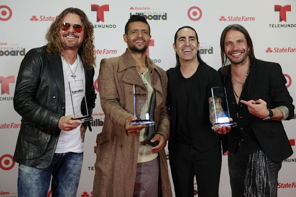 Robi Draco Rosa, second left, poses with members of Mana, Fher Olvera, left, Alex Gonzalez, and  Sergio Vallin, right, with their three awards at the Latin Billboard Awards in Coral Gables, Fla. Thursday, April 25, 2013. (Photo by Carlo Allegri/Invision/AP)