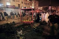 Pakistani security officials scan the site of a bomb explosion in Karachi. Twin bomb blasts killed six people, including a young girl, in a crowded market area of Pakistan&#39;s southern port city Karachi Tuesday, police and hospital officials said