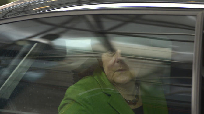 German Chancellor Angela Merkel looks out of her car window as she arrives for an EU summit Brussels on Thursday, March 14, 2013. European Union heads of state and government meet for a two-day summit, beginning Thursday, to discuss the current financial crisis. (AP Photo/Ezequiel Scagnetti)