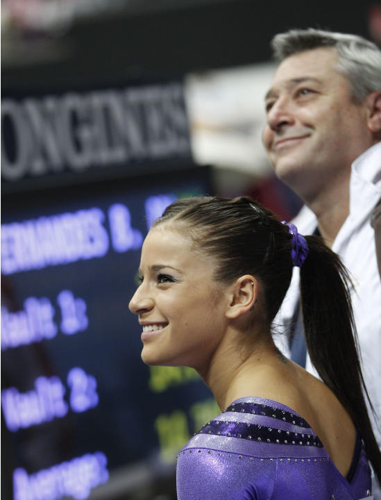 *RETRANSMISSION TO ADD ADDITIONAL INFORMATION* Gold medallist Alicia Sacramone of the U.S., foreground, and coach Mihai Brestyan of the U.S. team smile as the results are announced after her performan