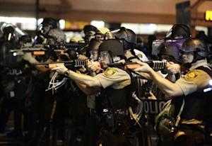 Police officers point their weapons at demonstrators …
