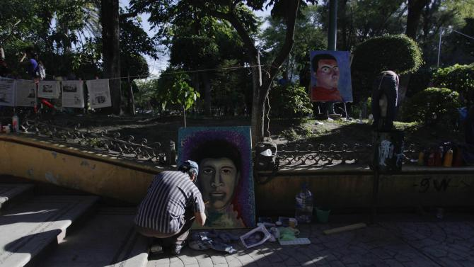 A painter works on a portrait of one of the missing 43 students of Ayotzinapa Teacher Training College, in Chilpancingo, in the southern Mexican state of Guerrero