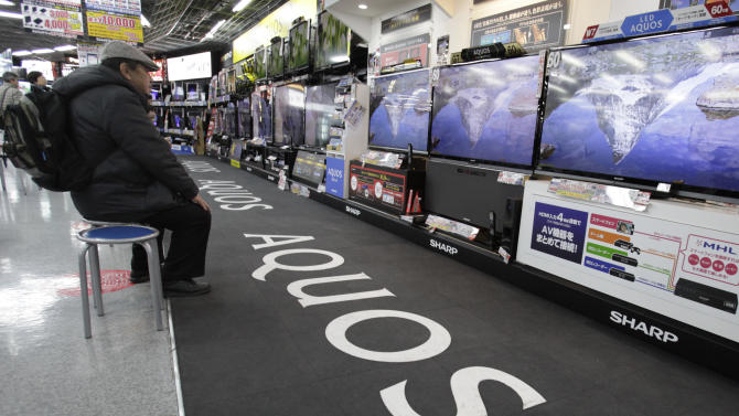 In this Jan. 31, 2013 photo, a shopper takes a look at Sharp's Aquos flat-panel TVs at an electronics store in Tokyo. Japanese electronics maker Sharp Corp. has reduced its quarterly losses but its outlook remains challenging. The Osaka-based company left its forecast for the full year ending March unchanged Friday, Feb. 1, at a 450 billion yen loss ($5 billion) as its flat-panel business for TVs and mobile devices gets hammered by plunging prices and intense competition. Sharp reported a 36.7 billion yen ($399 million) net loss for the October-December period, a smaller flow of red ink than its 173.6 billion yen loss a year earlier. It posted an operating profit for period, the first time in five quarters. (AP Photo/Shizuo Kambayashi)