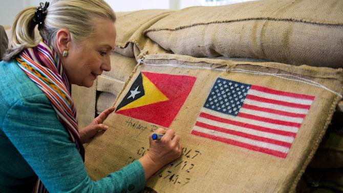 U.S. Secretary of State Hillary Rodham Clinton autographs a coffee bean sack while visiting the Timor Coffee Cooperative in Dili, East Timor Thursday, Sept. 6, 2012. U.S. Secretary of State Hillary Rodham Clinton is in East Timor to offer the small half-island nation support as it ends its reliance on international peacekeepers. (AP Photo/Jim Watson, Pool)