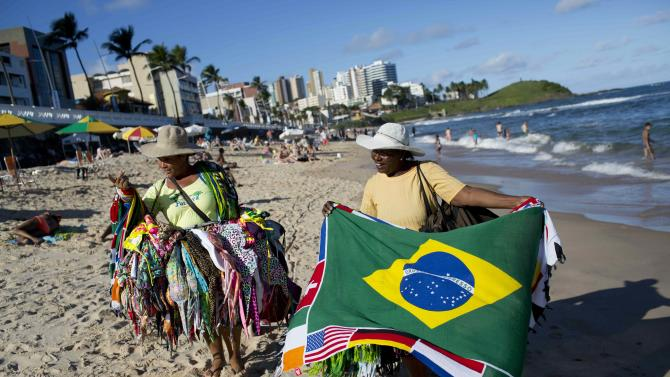 Street vendors sell swim wear and a Brazilian flags on the beach in Salvador, Brazil, Monday, June 30, 2014. Salvador is on of the host cities of the FIFA 2014 Soccer World Cup. (AP Photo/Rodrigo Abd)